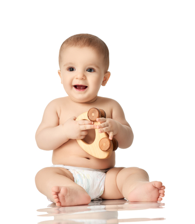 9 month infant child baby girl toddler sitting in white shirt with wood car toy isolated on a white background Stock Photo