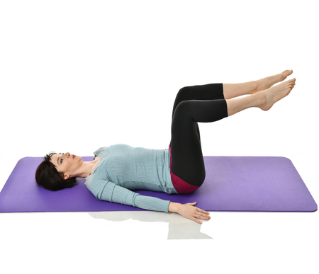 Mother woman exercising doing postnatal workout. Female fitness instructor stretching hands and legs in gym work out exercises for abdominals with athletic muscle body isolated on white background