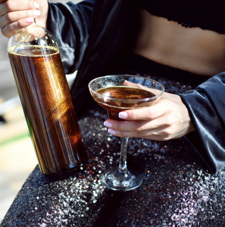 Beautiful fashion woman drink gold glitter martini cosmopolitan cocktail in restaurant cafe