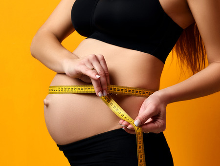 Pregnancy concept. Pregnant woman measure her belly with tape measure on yellow background