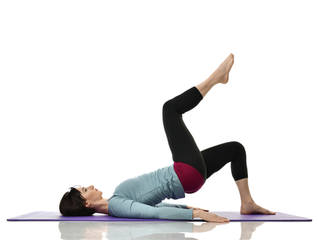 Mother woman exercising doing postnatal workout. Female fitness instructor holds legs in gym and workout exercises for abdominals with athletic muscle body over white background