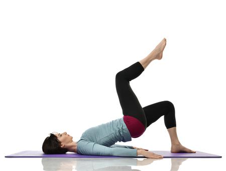 Madre donna esercizio facendo allenamento postnatale. Istruttore di fitness femminile tiene le gambe in palestra e esercizi di allenamento per addominali con corpo muscolare atletico su sfondo bianco
