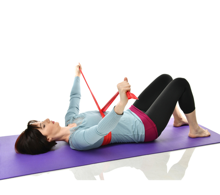 Woman exercising doing postnatal workout. Female fitness instructor working out with a rubber resistance band isolated on white background