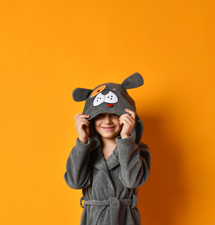 Boy kid standing in gray bathrobe looking at the corner on yellow background Stock Photo