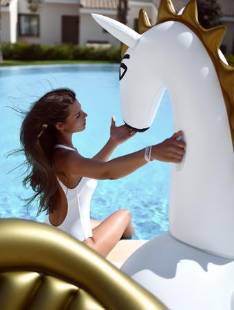 Young fashion woman relaxing in luxury swimming pool resort hotel on big inflatable unicorn pegasus float mattress in white bikini