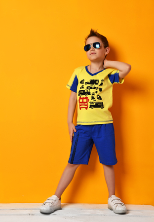 Preschool boy kid standing in blue tshirt with cars and shorts in sunglasses looking up on yellow background