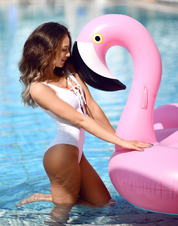 Young sexy pretty woman relaxing in a swimming pool resort hotel leisure with giant inflatable giant pink flamingo float mattress in white bikini