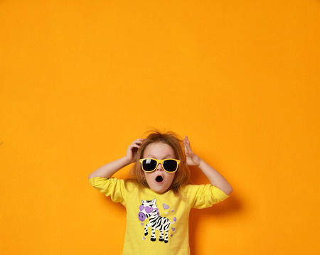 Young baby girl child kid surprised screaming in yellow zebra shirt and sunglasses with text space