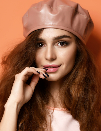 Young sexy brunette woman in leather beret hat on orange background Stock fotó