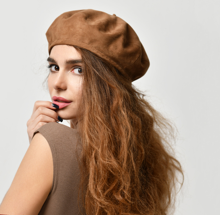 Young sexy brunette woman in brown beret hat looking at the corner  on gray background Stock fotó