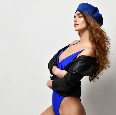 Young sexy brunette woman in blue beret hat looking at the corner with closed eyes  on gray background Stock fotó
