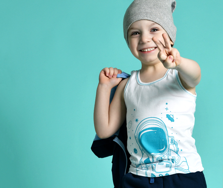 Preschool boy kid standing in white shirt and gray hat in shorts show two fingers peace sign on green mint background Imagens
