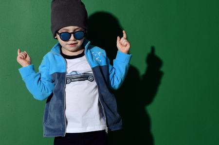 Preschool boy kid standing in blue zip-up sweatshirt and gray hat in shorts and sunglasses happy pointing hand on green mint background
