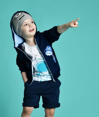 Preschool boy kid standing in blue zip-up sweatshirt and gray hat in shorts  pointing hand on green mint background Imagens