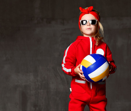 Volleyball girl kid hold and kick ball in red costume on grey concrete wall background