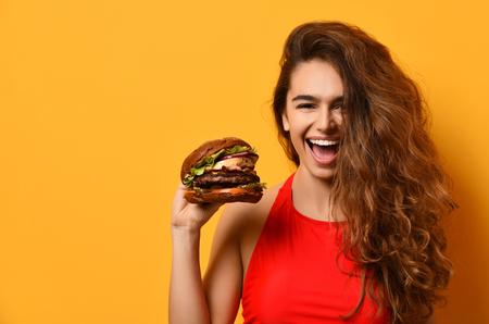 Vrouw houdt grote barbecue hamburger sandwich met hongerige mond gelukkig schreeuwen lachen op gele achtergrond. Snel voedselconcept.