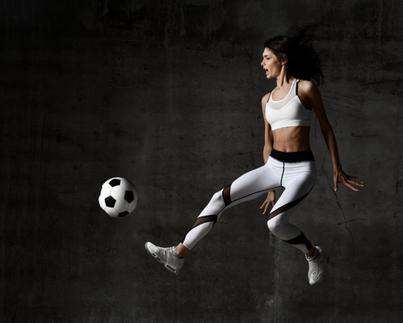 Soccer woman player jumps and hit the ball strike in the middle on concrete loft wall background. Black and white image