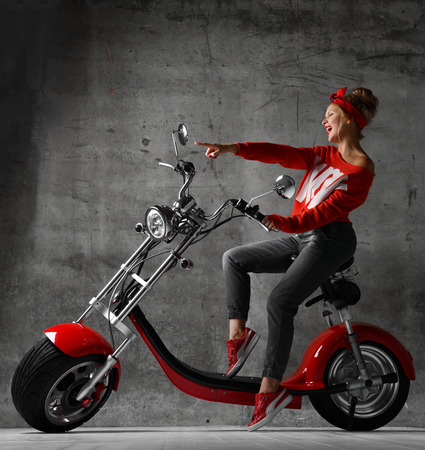 Woman ride sit on motorcycle bicycle scooter pinup retro style laughing smiling pointing hand at the corner in red blouse and jeans on concrete wall background looking at the corner