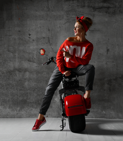 Woman sitting on motorcycle bicycle scooter  retro pinup style pointing finger at the corner in red blouse and jeans on concrete wall background looking at the corner