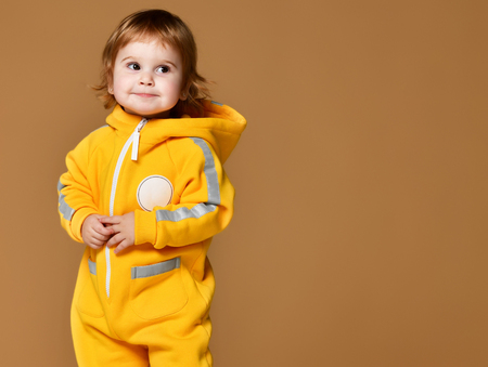 Infant child baby girl kid toddler in winter yellow overalls looking at the corner smiling on brown background
