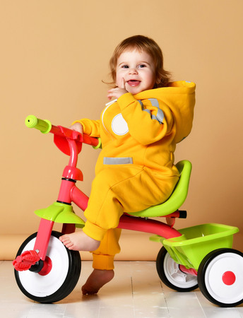 Baby girl kid riding her first bicycle tricycle in warm yellow overalls looking up on light grey background