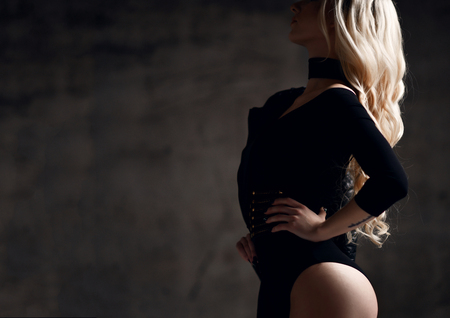 Young sexy blonde fashion woman standing in black body cloth and choker on dark night  light background