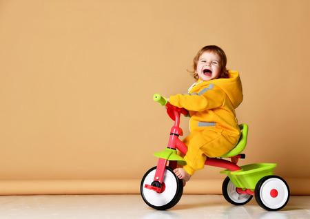 Babymädchen, das ihr erstes Fahrraddreirad in warmen gelben Overalls fährt und auf schreiendem grauem Hintergrund aufschaut
