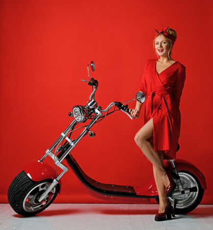 Woman pinup style ride new electric car motorcycle bicycle scooter present for new year 2019 in red dress smiling on red background