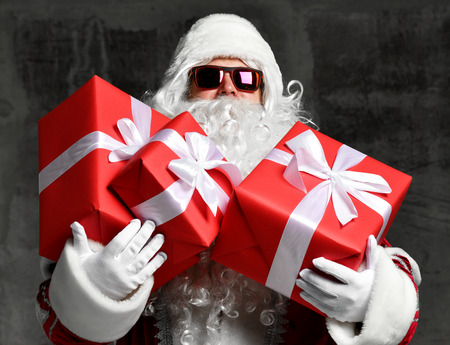 Santa Claus with red presents gifts for new year and sunglasses. Merry Christmas and happy New Year holidays concept