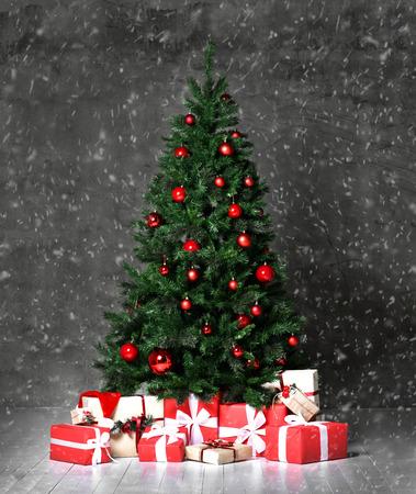 Árbol de Navidad decorado con adornos de patchwork rojo, bolas artificiales, regalos artesanales para el año nuevo 2019 en nieve de pared oscura Foto de archivo
