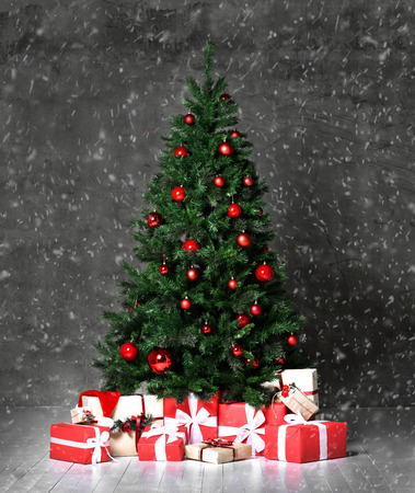 Arbre de Noël décoré de boules artificielles d'ornement patchwork rouge présente pour le nouvel an 2019 sur la neige du mur sombre Banque d'images