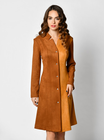 Young beautiful woman posing in new brown suede winter fashion dress smiling on a white Standard-Bild