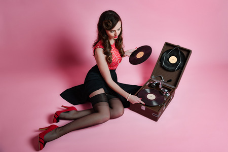 Vintage   of glamorous pinup girl sitting near retro gramophone holding LP vinyl record looking up on pink