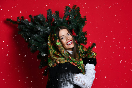 Happy Russian style woman hold Christmas  tree on her shoulders happy smiling laughing under snow on red background