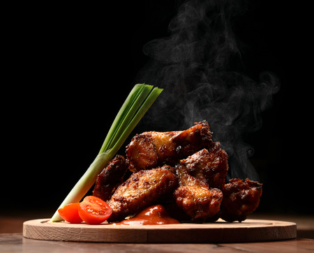 Hot and spicy bbq chicken wings with dip and hot sauce on wooden plate with steam smoke and vegetables Imagens
