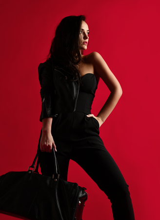 Beautiful sexy woman in black leather jacket and bra underwear hold bag with  red lipstick rouge on red background looking at the corner Фото со стока
