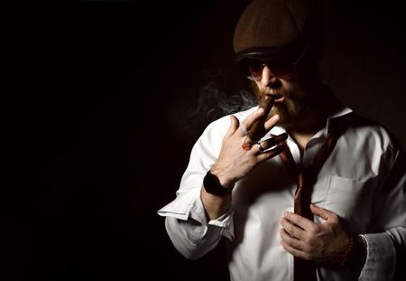 Brutaler Geschäftsmann, der Zigarre in brauner Sonnenbrille, weißem Hemd und Hut auf dunklem Hintergrund raucht Standard-Bild