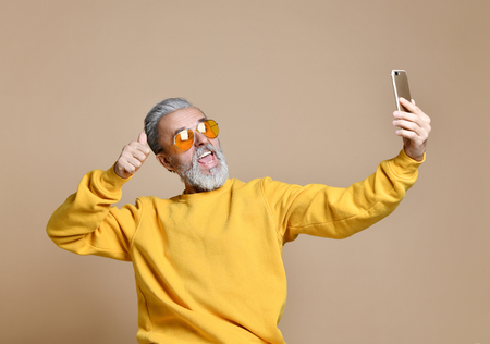 Portrait of happy senior millionaire man using smartphone cellphone make selfie in yellow sunglasses stylish fashionable men senior thumbs up