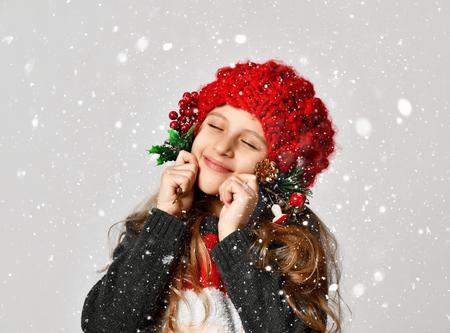 Weihnachtswinterkonzept - lächelndes kleines Mädchenkind im roten Hut des Weihnachtsmannes, der glücklich auf weißem Hintergrund unter Schnee lächelt Standard-Bild