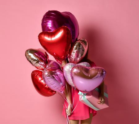Chica con corazones de colores globos de aire escondidos detrás de la fiesta de cumpleaños divirtiéndose y celebrando con un globo de color pastel de regalo