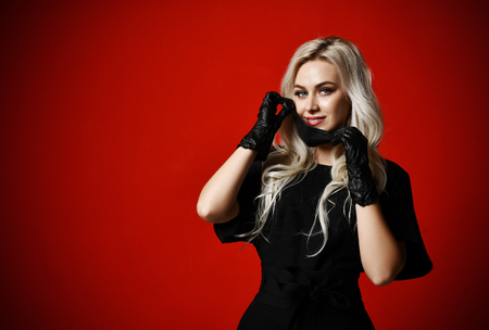 Beautiful woman in protective black medical mask and gloves on dark red background looking at the corner with free text space Banque d'images