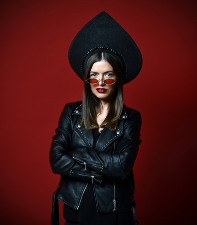 Woman in new modern fashion leather jacket in sunglasses and Russian style kokoshnik hat on dark red background Stock Photo