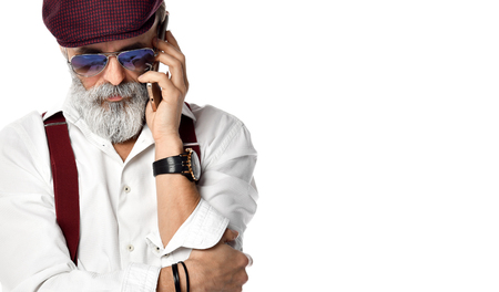 Old brutal senior millionaire man in cap talking on the mobile phone in aviator sunglasses stylish fashionable men isolated on white background Banco de Imagens