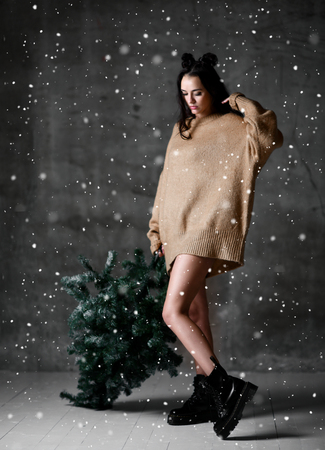 Beautiful hipster woman with Christmas fir tree in sexy knitted sweater blouse under heavy snow in loft room ready for New Year Celebration