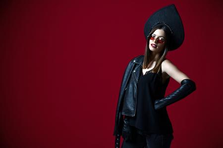 Portrait of brunette woman new fashion sunglasses and Russian traditional style kokoshnik hat on dark red background Stock Photo