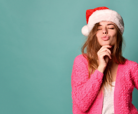 Beautiful female model wear xmas santa hat happy smiling kissing in pink blouse on blue mint background Stock Photo