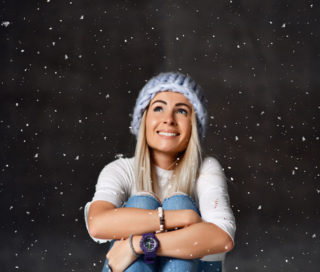 Blonde woman in light blue knitted hat happy smiling sitting under snowflakes winter time concept