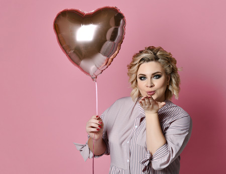 Woman with heart balloon on pink background blowing kiss. Love valentines day concept
