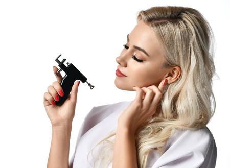 Woman beautician cosmetologist hold Ear Piercing Gun looking at the corner isolated on white background