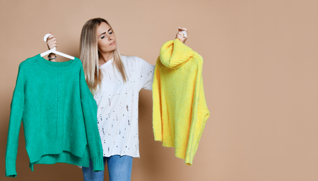 Woman shopping Christmas sale choose between two sweaters blouse green and yellow happy smiling on beige background Фото со стока
